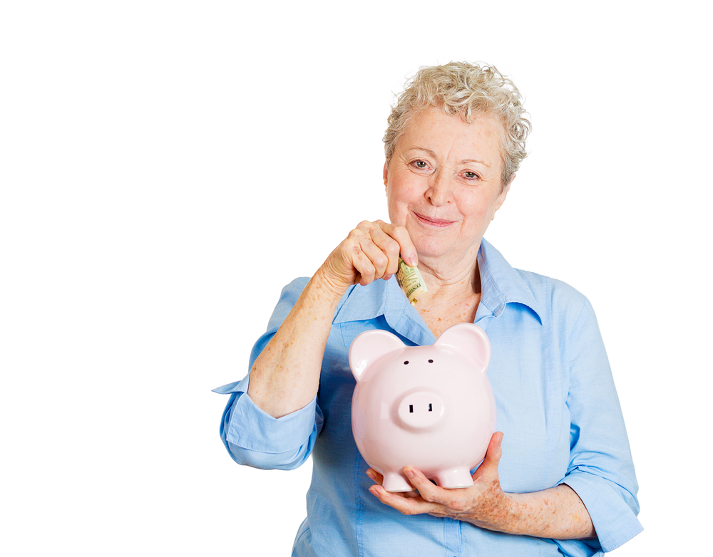 Closeup portrait of smiling senior mature woman depositing money into piggy bank, isolated on white background. Smart currency financial investment wealth decisions. Budget management and savings